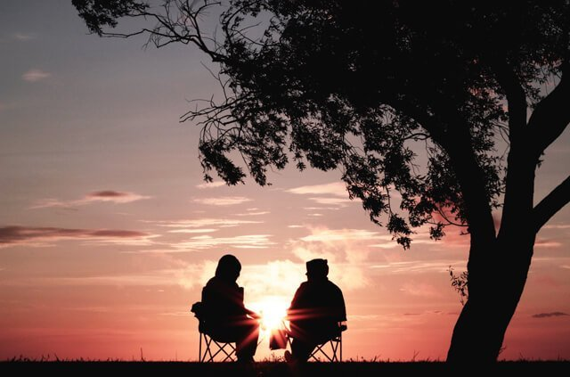 Photo of two people talking in a sunset